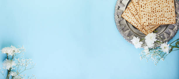 Pesah celebration concept - jewish Passover holiday Pesah celebration concept - jewish Passover holiday Background matzo and seder plate with white flowers on a blue background. View from above. Flat lay banner. passover stock pictures, royalty-free photos & images