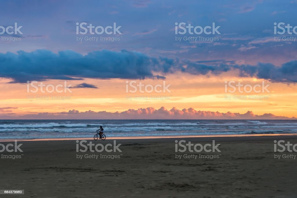 Pessoa andando de bicicleta no fim de tarde stock photo