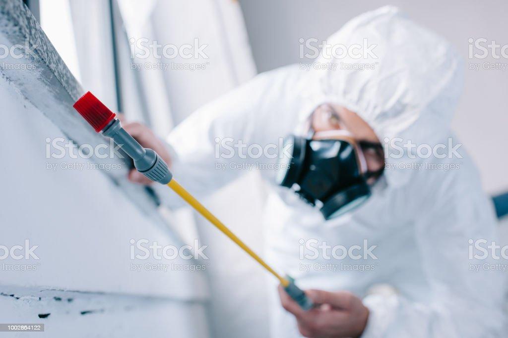Pest Control Worker Spraying Pesticides Under Windowsill At