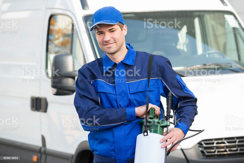Pest Control Worker With Pesticide Against Truck stock photo