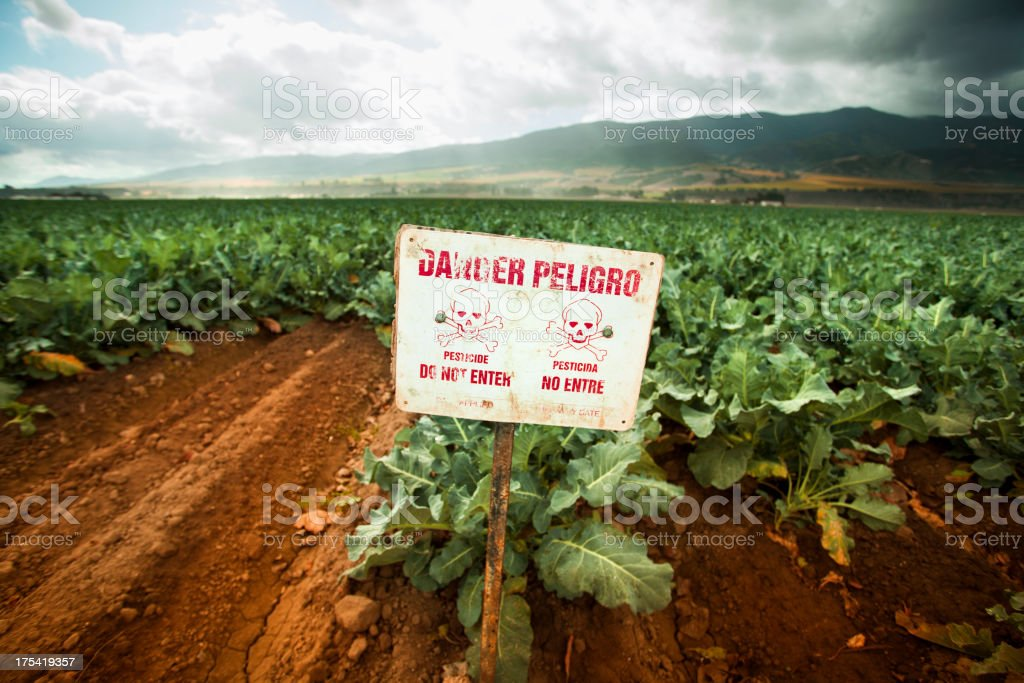 Pesticide warning sign on fertile farm land stock photo