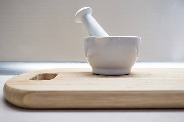 Pestle and Mortar on a Wooden Chopping Board Side View stock photo