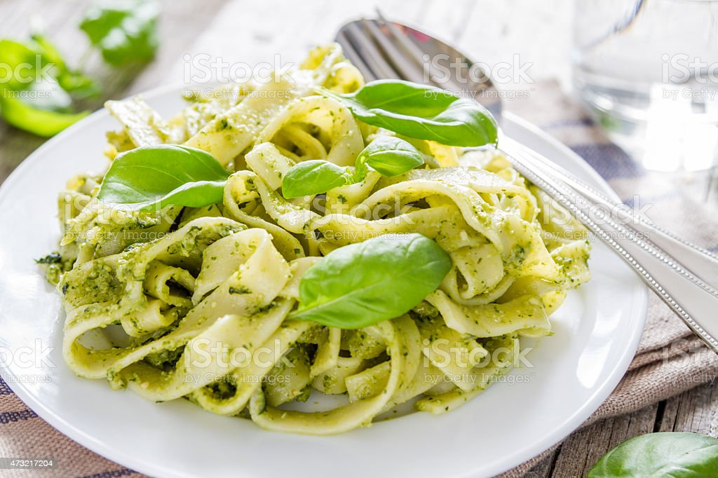 Pesto pasta with basil leaves on a white plate stock photo
