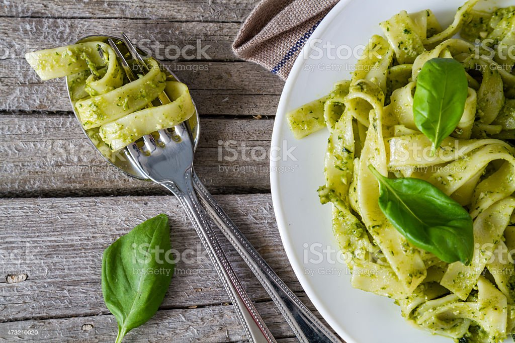 Pesto pasta wrapped around a fork next to a plate with pasta stock photo