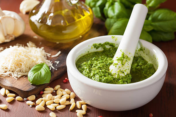 pesto sauce and ingredients over wooden rustic background stock photo