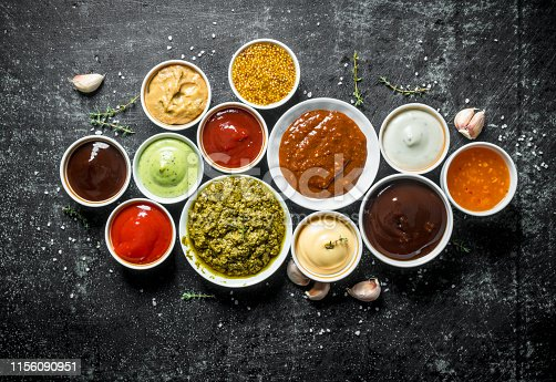 Pesto sauce, guacomole, ketchup, mustard, barbecue sauce in bowls. On dark rustic background