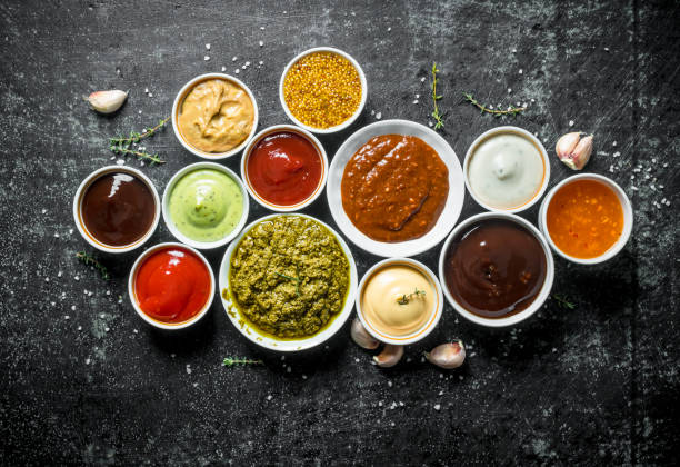 Pesto sauce, guacomole, ketchup, mustard, barbecue sauce in bowls. Pesto sauce, guacomole, ketchup, mustard, barbecue sauce in bowls. On dark rustic background dipping sauce stock pictures, royalty-free photos & images