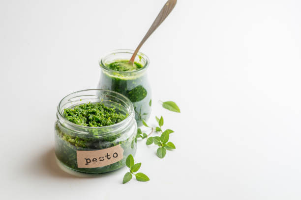 pesto sauce in a jar with a signed label on a white background stock photo