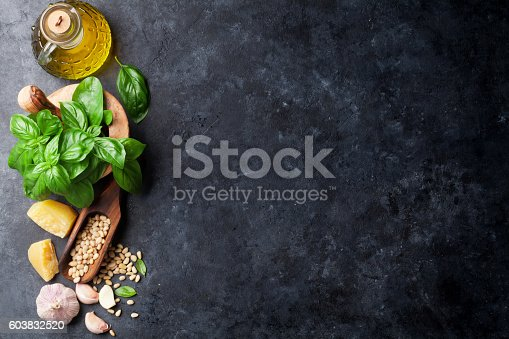 Pesto sauce cooking. Basil, olive oil, parmesan, garlic, pine nuts. Top view on dark stone table with copy space for your text