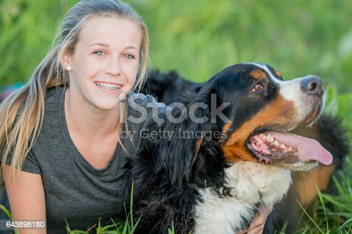 A young girl is outside with her dog on a sunny summer day. She is smiling and looking at the camera.