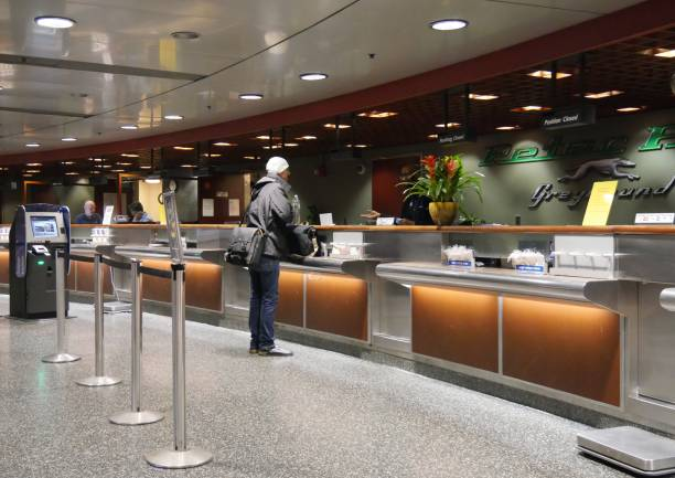 Peter Pan Greyhound ticket counter at the South Station in Boston BOSTON, MASSACHUSETTS—SEPTEMBER 2017: A man buys a bus ticket from the Peter Pan Greyhound ticket counter at the South Station in Boston. peter pan stock pictures, royalty-free photos & images