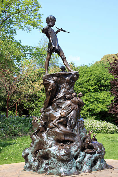 Peter Pan Statue London, United Kingdom, Apr 17, 2011 : The Peter Pan statue in Kensington Gardens. The statue shows the boy who would never grow up, blowing his horn on a tree stump with mice, fairies and squirrels in a leafy glade peter pan stock pictures, royalty-free photos & images