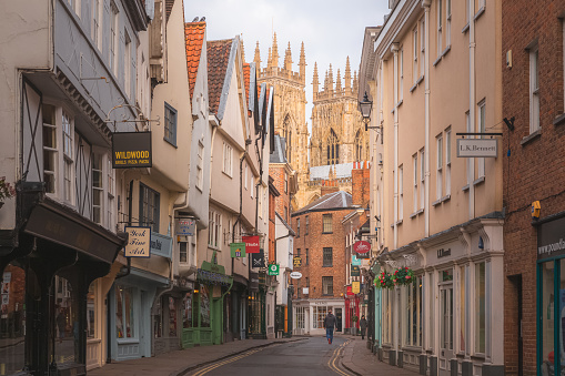 Street view of the top of York Minster in York, North Yorkshire from the shopping high street Petergate.