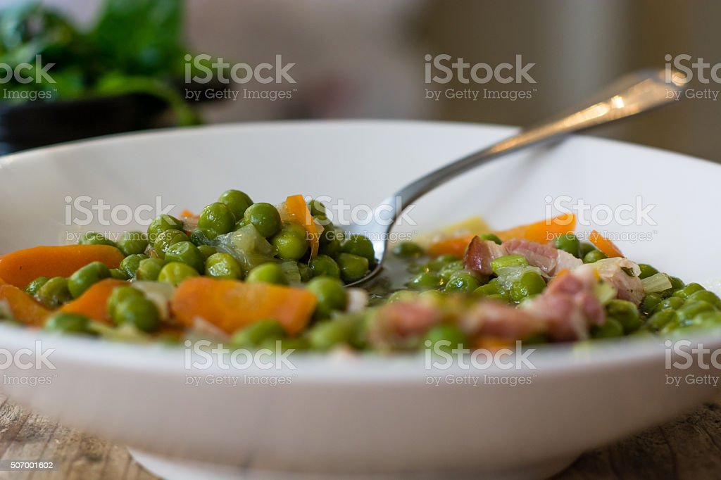 Petit pois a la Francaise in bowl with spoon stock photo
