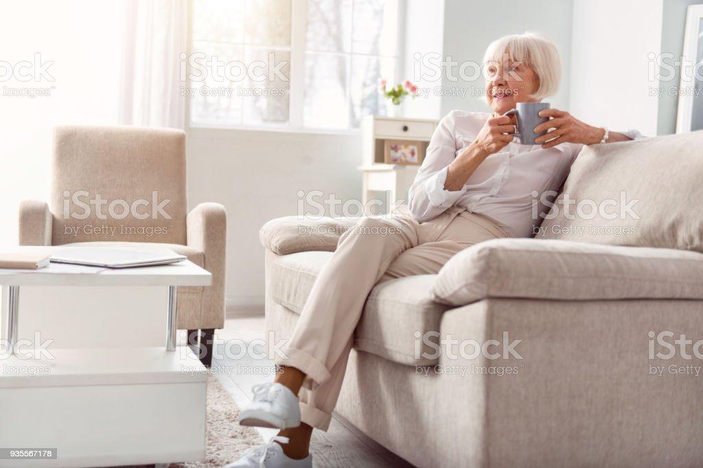 Petite anciana tomando café en su sala de estar foto de stock libre de derechos