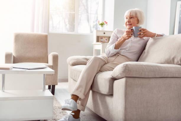 zierliche seniorin kaffeetrinken in ihrem wohnzimmer - seniorenwohnungen stock-fotos und bilder