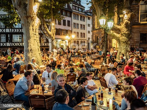 Strasbourg France , August 07th of 2018 People sitting in an outdoor cafe at night at the Petit France quarter in Strasbourg France. This historic part of the city is considered a Unesco Heritage site with old half timbered houses from the XVO and XVII century and surrounded by canals. Nowadays it is a very visited travel destination.