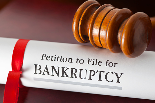 182148217 istock photo Petition to file for bankruptcy under a gavel 180817949