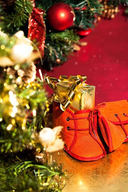 petits chaussons au pieds d'un sapin de Noël petits chaussons rouges de bébé remplis de cadeaux au pieds du sapin de Noël sapin noel stock pictures, royalty-free photos & images
