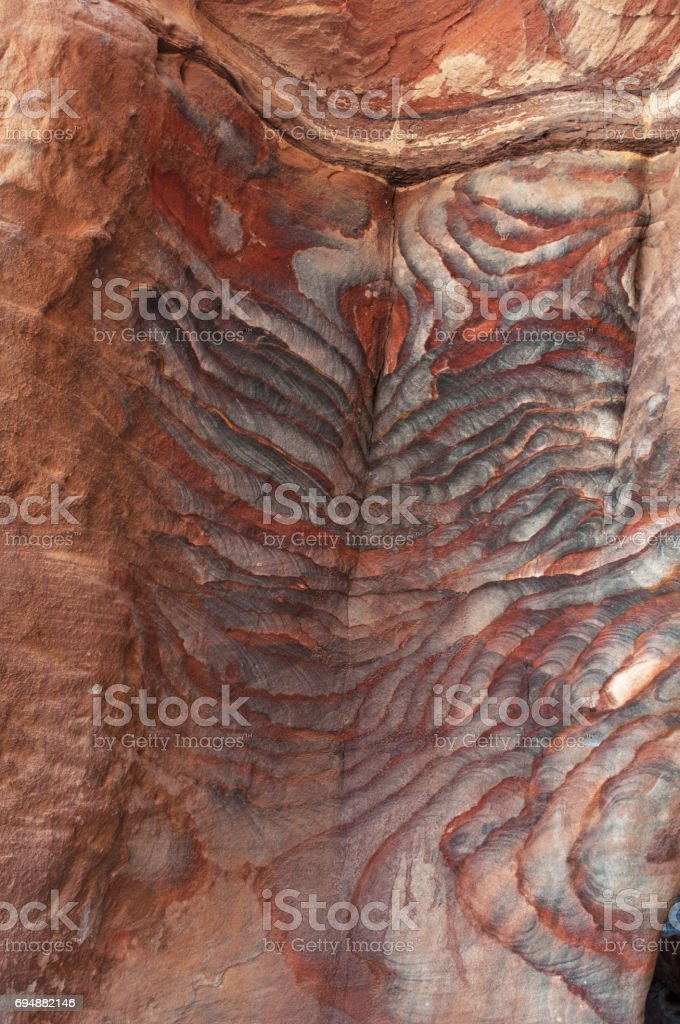 Petra: veins of different shapes, colors and shades on the red rocks of the Royal Tombs, huge funerary structures carved into the rock face in the archaeological city of Petra stock photo