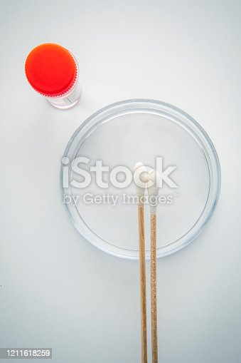 A petri dish with a cotton swabs and specimen bottle.