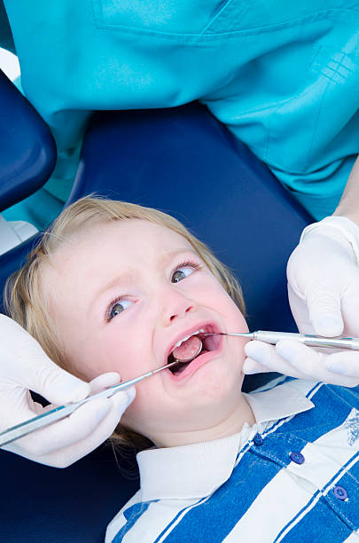 A petrified child at the dentist stock photo