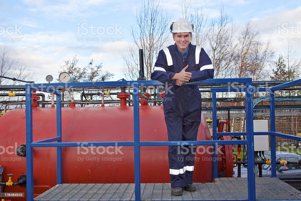 Petrochemical contractor posingl in front of an oil refinery royalty-free stock photo