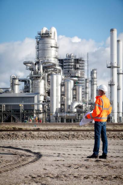 petrochemischer inspektor mit zeichnung - destillationsturm stock-fotos und bilder