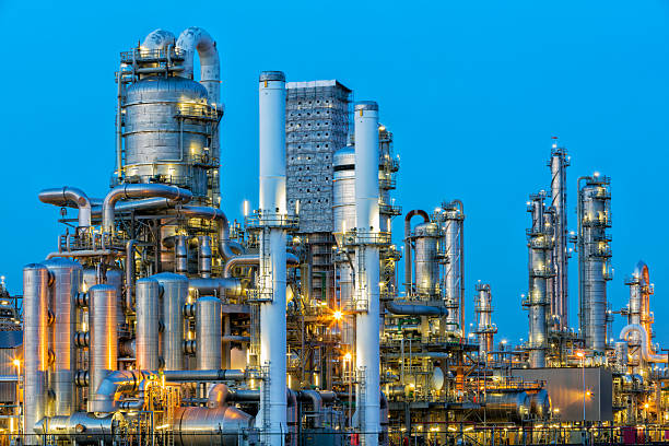 petrochemical plant illuminated at dusk - refinery stock photos and pictures
