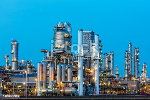 A large, modern petrochemical plant at dusk in industrial district near Rotterdam, Netherlands, Benelux, Europe. Distillation towers and other installations are visible against blue sky. 50 megapixel image taken with Canon EOS 5Ds, digital blending technique, long exposure with tripod.