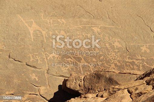 Jordan, Wadi Rum village - January 06, 2020: Petroglyphs (Alameleh inscriptions) of a caravan of camels on the sandstone rock in Wadi Rum desert in Jordan.