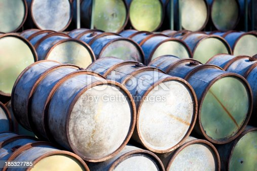 rusty blue petrol barrels in shade