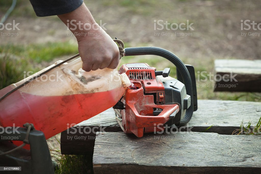 Petrol powered two stroke chainsaw refueling stock photo