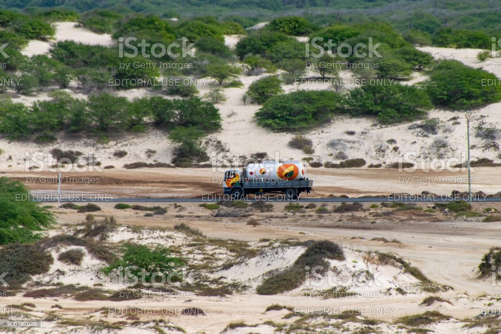 Petrol tanker driving along a dusty road stock photo