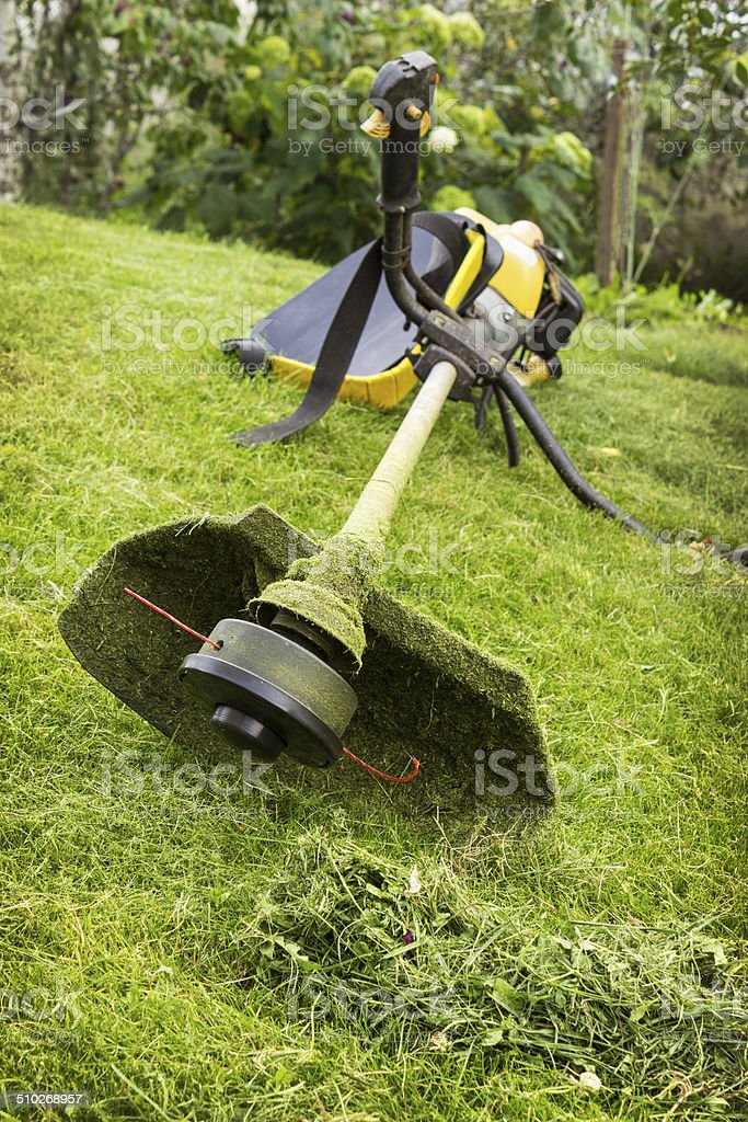 Petrol trimmer on the sloped lawn stock photo