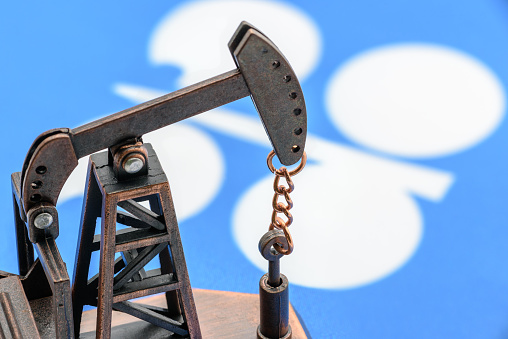 Petroleum, petrodollar and crude oil concept : Oil pump jack and flag of OPEC or Organization of Oil Exporting Countries, depicts the investment in the development or production of global oil industry
