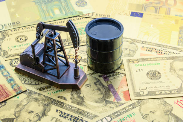 Petroleum, petrodollar and crude oil concept : Pump jack and a black barrel on US USD dollar notes, depicts the money received or earned from sales after investment in the development of oil industry. stock photo