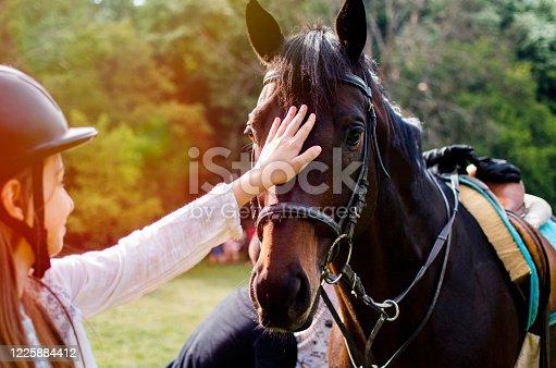 Teenage Girl Jockey cuddling a Horse Head outdoors. Close up view