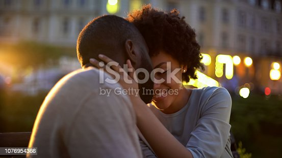 Petty woman tenderly stroking boyfriends face, love expression, nuzzling on date