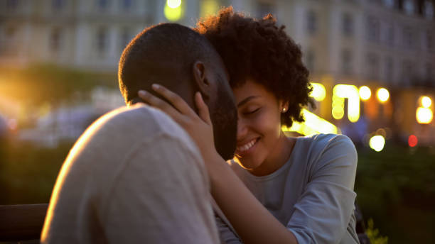 Petty woman tenderly stroking boyfriends face, love expression, nuzzling on date Petty woman tenderly stroking boyfriends face, love expression, nuzzling on date date night romance stock pictures, royalty-free photos & images
