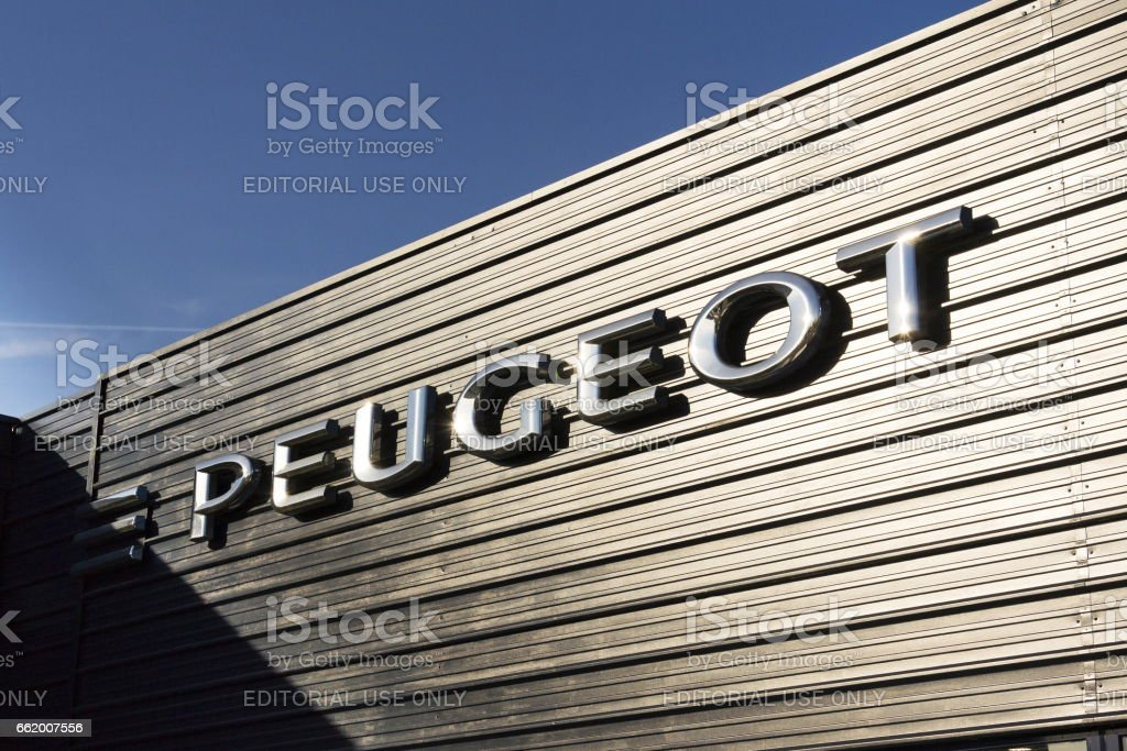 Peugeot car company logo in front of dealership building stock photo