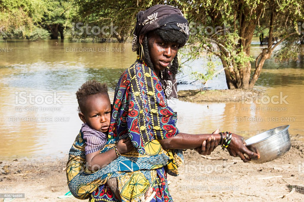 Peul Nomad woman with baby at the water pond. stock photo