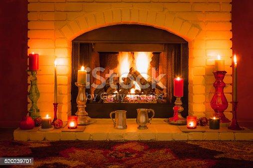 istock Pewter mugs on candle filled burning fireplace (P) 520239701