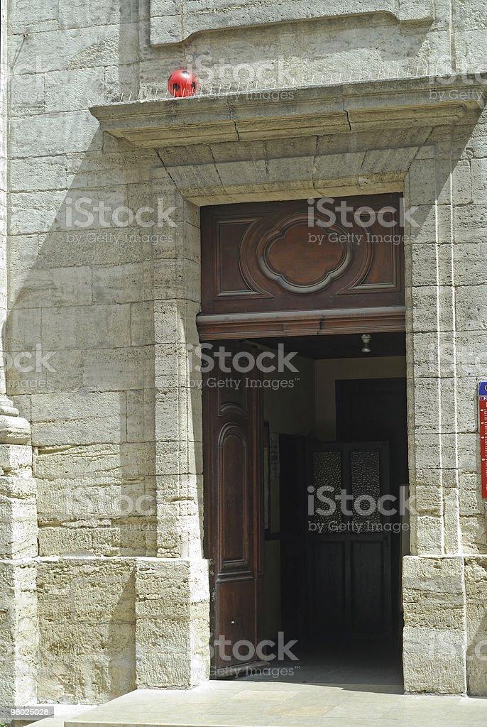 Pezenas (Francia)-ball rosso perso oltre una porta foto stock royalty-free
