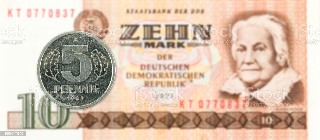 5 pfennig coin against historic 10 east german mark bank note royalty-free stock photo