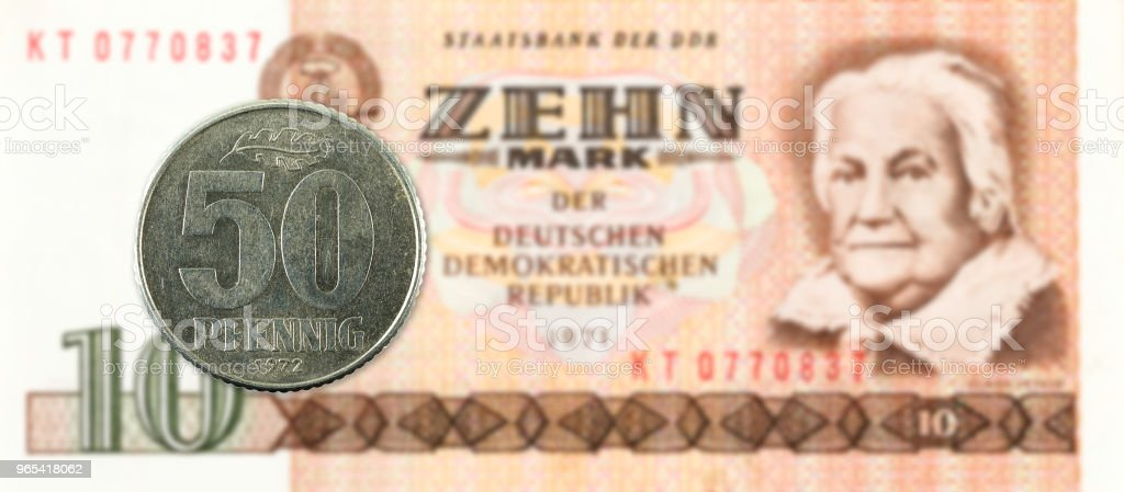50 pfennig coin against historic 10 east german mark bank note royalty-free stock photo