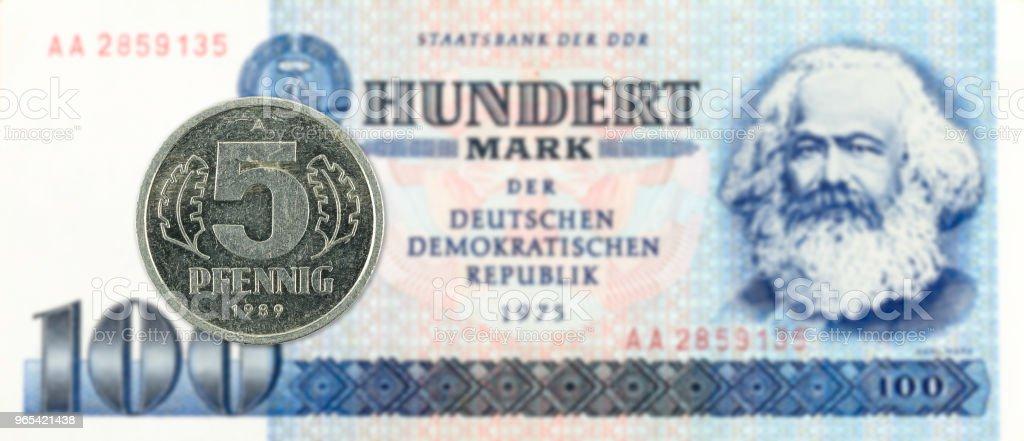 pièce 5 pfennig contre historique 100 billets de Banque du mark est-allemand - Photo de Activité bancaire libre de droits