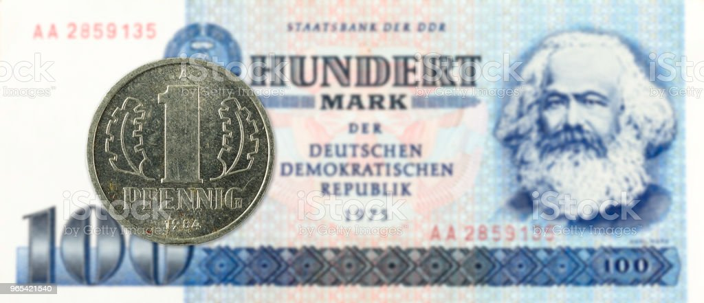 1 pfennig coin against historic 100 east german mark bank note royalty-free stock photo