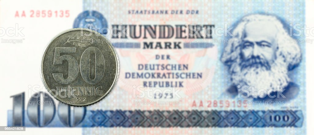 50 pfennig coin against historic 100 east german mark bank note royalty-free stock photo