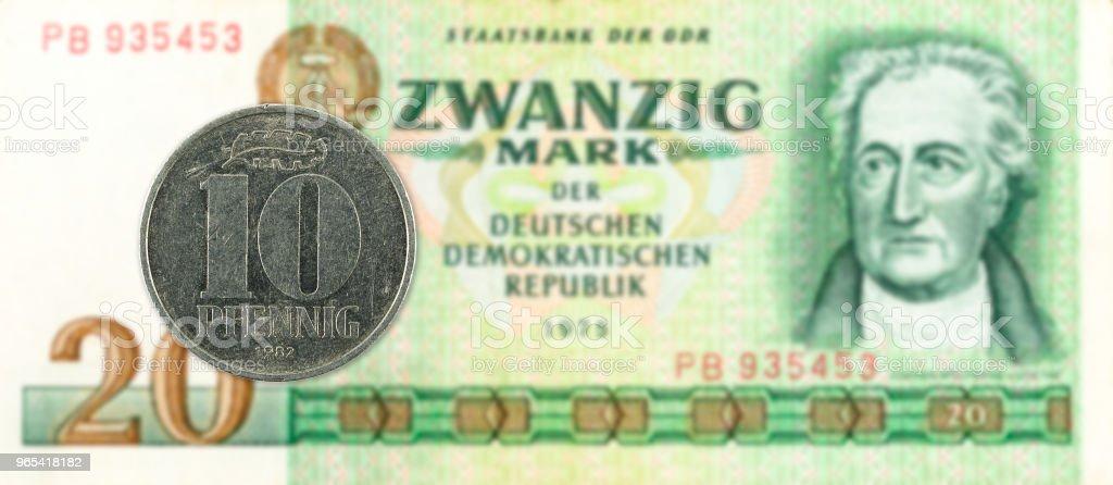 10 pfennig coin against historic 20 east german mark bank note zbiór zdjęć royalty-free